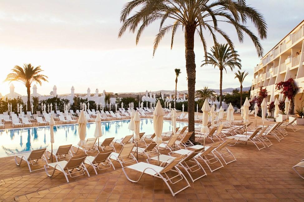 Rikelig med solsenger og parasoller rundt bassengene